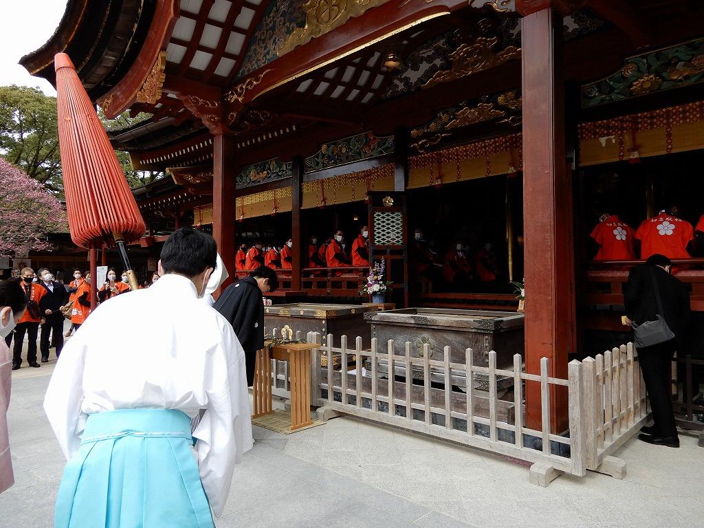 拝殿に前に結婚式の一行が見え拍手する初老たち
